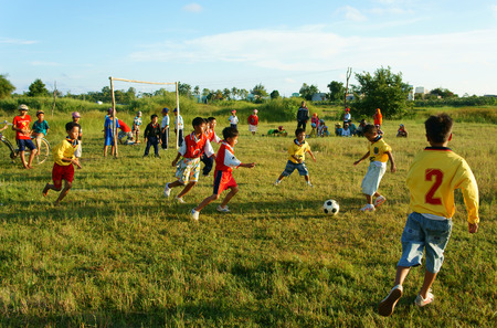 BINH THUAN, VIETNAM: Group of Asian kid playing football in team, Vietnamese little boy run on grass, outdoor activity of children physical education at countryside, Viet Nam, Oct 26, 2014 Editorial
