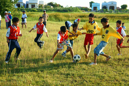 BINH THUAN, VIETNAM: Group of Asian kid playing football in team, Vietnamese little boy run on grass, outdoor activity of children physical education at countryside, Viet Nam, Oct 26, 2014