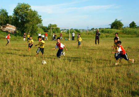physical education: BINH THUAN, VIETNAM: Group of Asian kid playing football in team, Vietnamese little boy run on grass, outdoor activity of children physical education at countryside, Viet Nam, Oct 26, 2014 Editorial