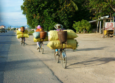 PHAN RANG, VIET NAM- OCT 22: Group of Asian woman ride cycle on highway, women transfer overload bag,  trafiic in danger, unsafe situation at Vietnamese country road on day, Vietnam, Oct 22, 2014