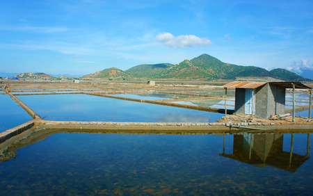 Beautiful landscape of saline filed on day under blue sky, store house reflect on saltwater, chain of mountain behind, amazing scene of agriculture at Vietnamese countryside