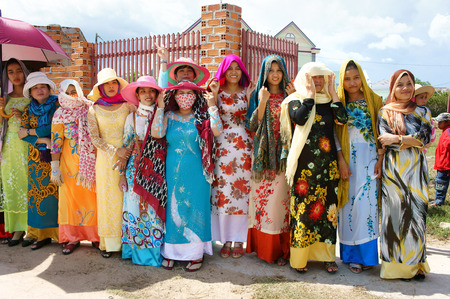 PHAN RANG, VIET NAM- OCT22: Group of beautiful Vietnamese woman in tradition dress  (ao dai) standing on street with happy smile, attend Kate carnival, traditional culture of Cham people, Vietnam, 2014 Editorial