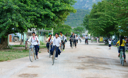 togheter: PHAN RANG, VIET NAM- OCT 22: Group of Unidentified Asian children riding bike on country road to coming home, boy and girl pupil of Vietnamese countryside have to move by bicycle, Vietnam, Oct22, 2014
