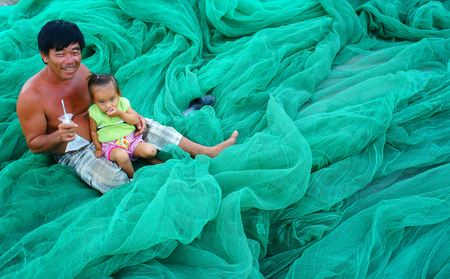 PHAN RANG, VIET NAM- OCT 23: Asian grandfather carry kid, sitting on fishing net at Vietnamese fishing village, happy family with old and young people,  smile face on cyan color, Vietnam, Oct 23, 2014