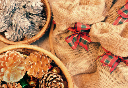 x mass: Xmas gift and pine cone in basket, decoration for christmas season, present bag from burlap, with amazing knot