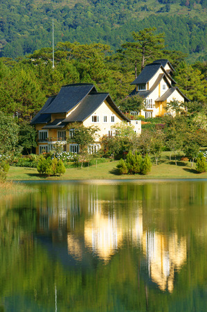 dalat: Beautiful landscape at Dalat village, group of villas reflect on lake, eco holiday resort among green pine forest, fresh air, pure environment, romantic scene for honeymoon at Da Lat, Vietnam