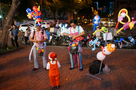 16 17: HO CHI MINH CITY, VIET NAM- DEC 17: Asia man in clown cloth, make comic character from colorful ballloon at Saigon street on holiday, street artist clever to bend  amazing shape, Vietnam, Dec 16, 2014