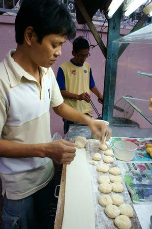 vietnamese food: HO CHI MINH CITY, VIET NAM- DEC 17: Vietnamese food at Sai gon street, fried dumplings is popular street food, fast food, family of vendor make dish on pavement, Saigon, Vietnam, Dec 17, 2014