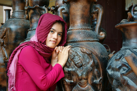 PHAN RANG, VIET NAM- NOV 22: Beautiful portrait of Cham girl, minority ethnic of Vietnamese, pretty women in traditional dress, sit beside pottery product, unique terracotta, Vietnam, Nov 22, 2014