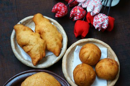 vac: Group of Vietnam street food: fried dumpling, quai vac cake, sponge cake make from wheat flour, good decoration on plate, wooden background, this Vietnamese snack is fastfood, rich cholestorol