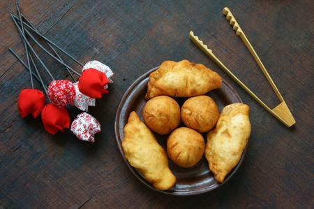 Group of Vietnam street food: fried dumpling, quai vac cake, sponge cake make from wheat flour, good decoration on plate, wooden background, this Vietnamese snack is fastfood, rich cholestorol
