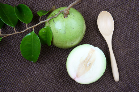 sua: Vietnam fruit, milk fruit or star apple or Vu Sua, is special farm product that only Viet nam exported, close up of this nutrition, organic fruit with green leaf on brown background Stock Photo