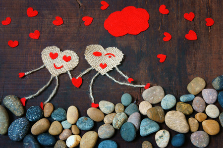 red pebble: Funny idea with symbol of happy couple, hand in hand walking on pebble, sky with red cloud, group of red heart, Valentine day is happiness for lover Stock Photo