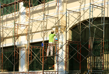 HO CHI MINH CITY, VIET NAM- FEB 6: Asian worker working on scaffold to renovate for architecture work, Vietnamese man work on day in unsafe situation to painting the wall, Saigon, Vietnam, Feb 6, 2015