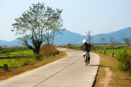 buon: BUON ME THUOT, VIET NAM- FEB 7: Vietnamese woman riding bicycle on country road, beautiful of natural landscape at Daklak countryside, Vietnam, Feb 7, 2014 Editorial