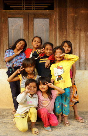 poor child: DAKLAK, VIET NAM- FEB 24: Group of unidentified Asian children standing, posing at wooden house of Vietnamese countryside, poor child, pretty girl happy and smiling, Dak Lak, Vietnam, Feb 24, 2015