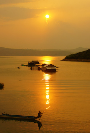 ka: Abstract Vietnamese rural at sunset, sun on yellow sky, vibrant color, silhouette of people rowing a row boat on Nam Ka Lake, Dakak, Vietnam, house on water, make amazing landscape of Viet Nam travel