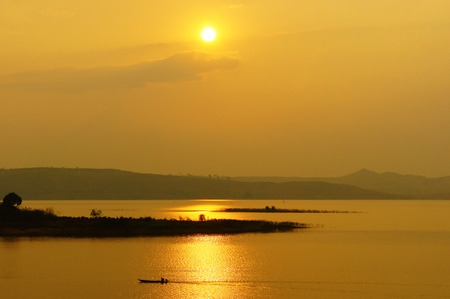 buon: Abstract Vietnamese rural at sunset, sun on yellow sky, vibrant color, silhouette of people rowing a row boat on Nam Ka Lake, Dakak, Vietnam, house on water, make amazing landscape of Viet Nam travel
