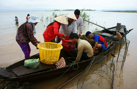 river fish: DONG NAI- VIET NAM- AUST 31: Group of Asian fisherman fishing on Tri An lake, a branch of Dong Nai river, crowd of people collect river fish on row boat, Vietnam, Aust 31, 2014