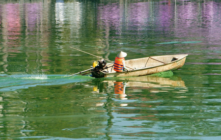 water colour: Asian sanitation worker working on  Xuan Huong lake, Dalat with polluted water by green algae, Vietnamese man sit on boat, the boat reflect on water, pollution of source water is big global problem
