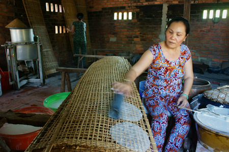 rice paper: BA RIA, VIET NAM- FEB 11: Asian woman sitting, working at home, Vietnamese female make rice paper from rice flour at banh trang trade village, smoke from firewood cooker, Vietnam, Feb 11, 2015 Editorial