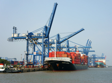 HO CHI MINH CITY, VIET NAM- FEB11: Transportation for export, import at Cat Lai port on Sai Gon river, crane load container to boat, this habour is big industry service for trade, Vietnam, Feb 11,2015