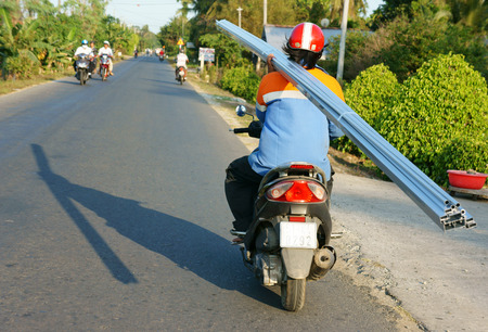 one hand: BEN TRE, VIET NAM- MAR 24: Transportation goods on street in danger by motorbike, Asian man ride one hand, carry heavy, overloaded traffic, this is unsafe, can make accident, Vietnam, Mar 24, 2015
