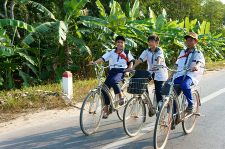 BEN TRE, VIET NAM- MAR 24: Group of three unidentified Asian pupil ride bicycle on country road to go to school, boys in uniform, happy with friendship, Vietnam, Mar 14, 2015 Editoriali