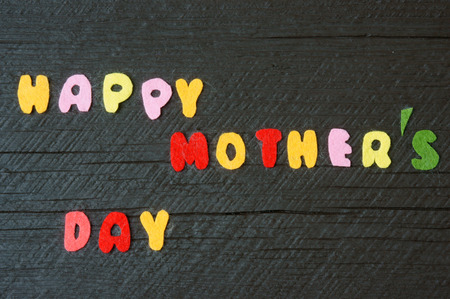 make a gift: Happy mothers day with i love mom message,  idea from colorful letter on wooden background, woman hand cutting character to make gift for mother on happy day, show feeling with mother, love family