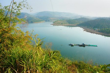 buon: Nice landscape of Vietnamese countryside, eco lake with floating house, mountain around with hill, green environment, fresh air, beauty place for Vietnam travel Stock Photo