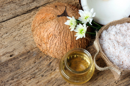 oil massage: Coconut oil, essential oil from nature, a skin care that safe, rich vintamin, use in massage at spa, organic cosmetic on wooden background Stock Photo