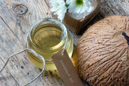 Coconut oil, essential oil from nature, a skin care that safe, rich vintamin, use in massage at spa, organic cosmetic on wooden background Stok Fotoğraf