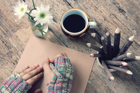 hand wear: Women hand wear wool gloves in wintertime, writting letter for lover from distant, lonely background in cold day of christmas season, hot coffee cup, flower pot, pencil on wooden background