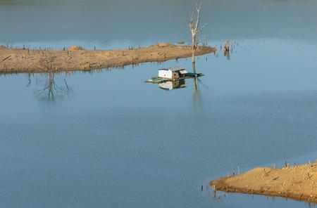 buon: Harmony landscape of Asia countryside lonely floating house on water beautiful Nam Ka lake at Daklak Viet nam. Reflection of dry tree home on river make beautiful scene