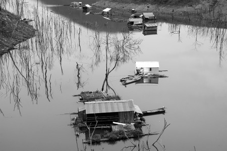 ka: Vietnam landscape in evening on black and white group of floating house on Nam Ka lake dry tree reflect on water make amazing scene of Asia countryside