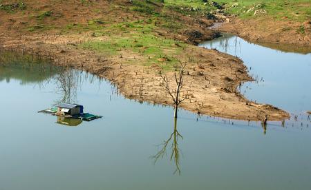 albero secco: L'armonia del paesaggio di campagna Asia casa galleggiante solitaria sull'acqua bellissimo lago Nam Ka a Daklak Viet nam. Riflessione di casa albero secco sul fiume fanno bella scena