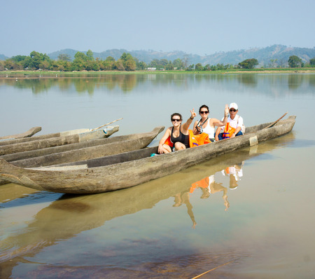 life jacket: BUON ME THUOT, VIET NAM- FEB 25: Traveller travelling on Lak Lake, caucasian tourist on rowing boat, wear life jacket, people happy with view at nature, Buonmethuot, Vietnam, Feb 25, 2015 Editorial