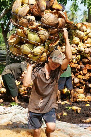 outside machines: BEN TRE, VIET NAM- JUNE1: Asian worker work hard outdoor on day, Vietnamese man transfer material from coconut fiber industry, tradition product from coconut area, Mekong Delta, Vietnam, June 1, 2015 Editorial