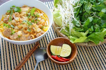 ensalada: Mi quang y materias primas como la carne de cerdo, ensalada, vegetales, chile, lim�n, amarillo fideos, camarones secos, Quang fideos es famosa comida vietnamita, muy delicioso comer Foto de archivo