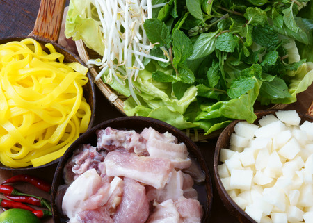 mi: Mi quang and raw material as pork meat, salad, vegetable, chilli, lemon, yellow noodle, dried shrimp, Quang noodle is famous Vietnamese food, very delicious eating