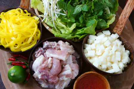vietnamese food: Mi quang and raw material as pork meat, salad, vegetable, chilli, lemon, yellow noodle, dried shrimp, Quang noodle is famous Vietnamese food, very delicious eating