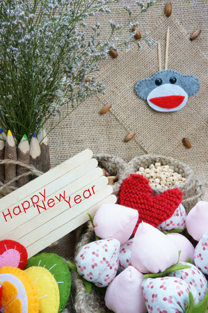 Art idea with funny monkey for happy new year 2016, new year eve time, handmade monkey face, clockwise, colorful  hand made fruit, fibre strawberry, flower decor on burlap background, vintage concept