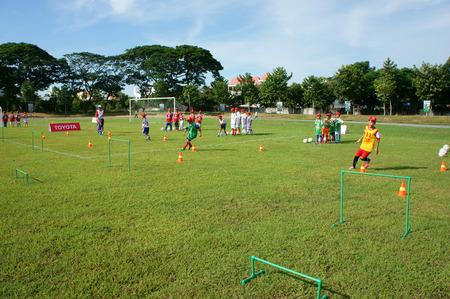 physical education: CAN THO, VIET NAM- JULY26: Unidentified Asian children playing football, summer activity, kid physical education, trainer training soccer for Vietnamese boy, teamwork spirit, Vietnam, July 26, 2015