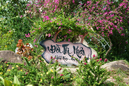 poem: Han Mac Tu, a fomous Vietnamese poet, short life artist, his grave at Genh Rang tourist area, Quy Nhon, Binh Binh, Viet Nam, poem in calligraphy on wooden background, stone hill, beauty nature Editorial