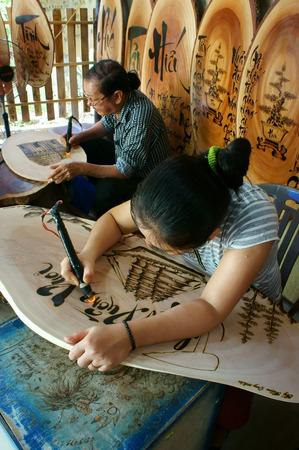 poem: QUY NHON, VIET NAM- AUG 23: Vietnamese artist doing wood engraving by fire pen, man engrave Han Mac Tu poem at souveir shop of Genh Rang tourist area, a famous poet, Quynhon, Vietnam, Aug 23, 2015