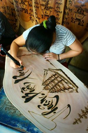 QUY NHON, VIET NAM- AUG 23: Vietnamese artist doing wood engraving by fire pen, man engrave Han Mac Tu poem at souveir shop of Genh Rang tourist area, a famous poet, Quynhon, Vietnam, Aug 23, 2015