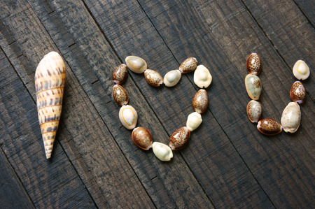 unrequited love: I love you message by shell on wooden background, heart shape, symbol of love with simplicity, idea for valentine day, mother day of father day