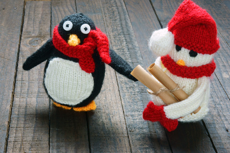 xmas background: Knitted Xmas ornament, handmade snowman, hand made penguin knit from red, white wool, this toy for christmas holiday, abstract background with pine cone, gift card, red heart