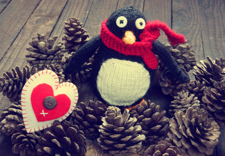 Knitted Xmas ornament, handmade snowman, hand made penguin knit from red, white wool, this toy for christmas holiday, abstract background with pine cone, gift card, red heart