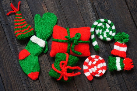 Christmas ornament for winter holiday, red and green knitted hat, scaft, sock, gift  in small size, symbol for xmas, noel season on december Imagens